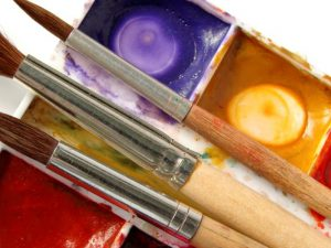 Three paintbrushes and paint palette
