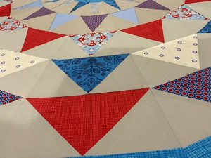 Patchwork quilt with blue and red patterned flags