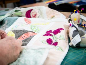 Hands working on a patchwork quilt with pin cushion