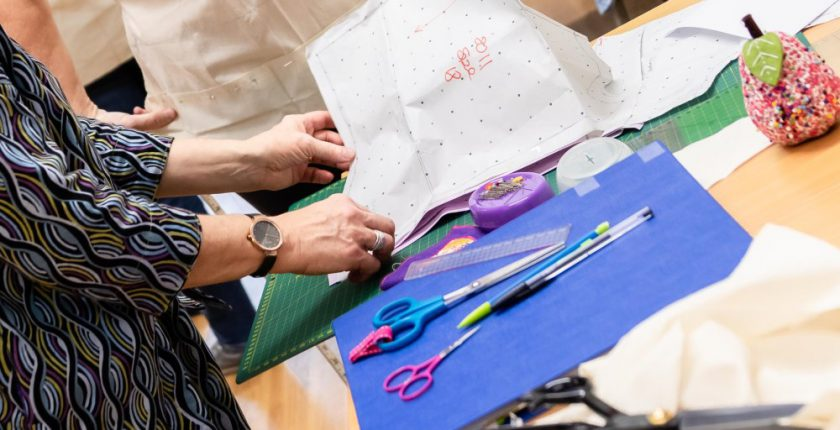 Hands cutting a pattern for sewing with blue fabric, pens and scissors