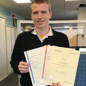 Young man with blond hair holding certificates