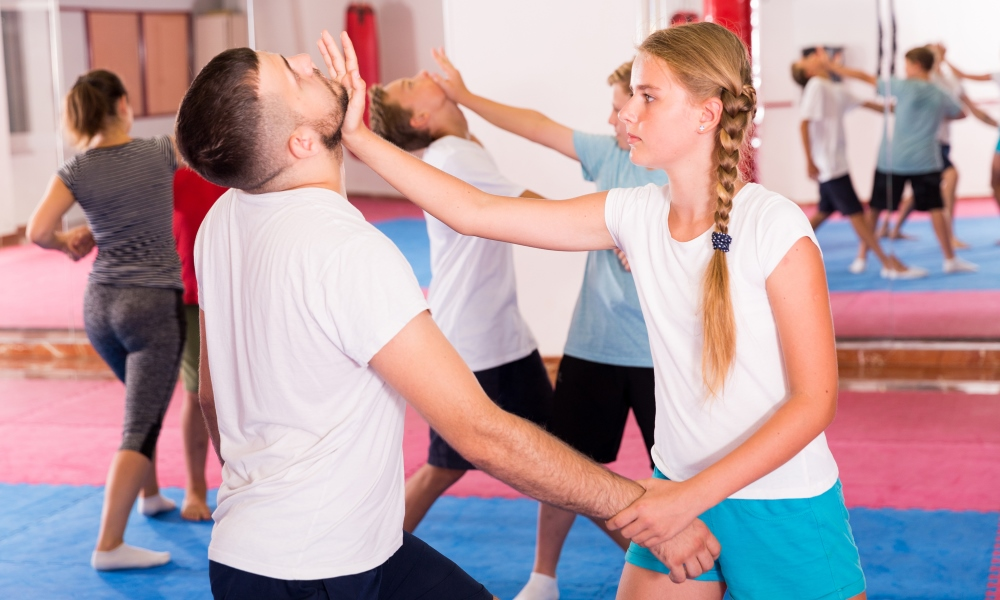Girl and man practising self-defence techniques
