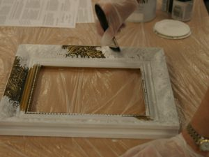 Hands painting a gold picture frame with white paint