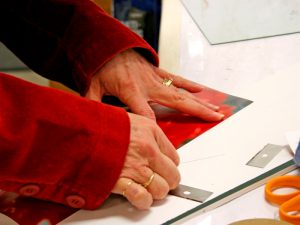 Woman cutting paper for a picture frame