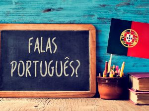 Blackboard with Falas Portugues written on it with Portuguese flag and pot of pencils