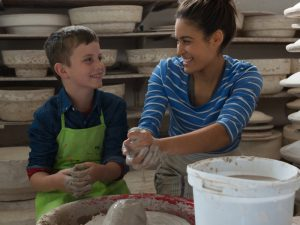 woman and child working on a pottery wheel