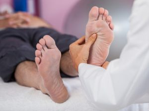 person practising reflexology on a man's feet