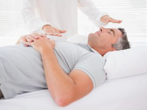 Man lying on bed with someone practising reiki