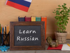 Blackboard with Learn Russian written with pencils and books behind
