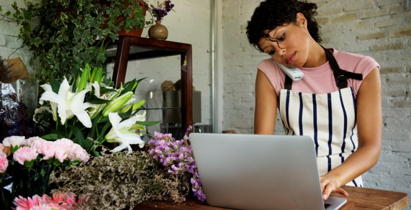 Lady wearing pink tshirt and stripy apron on telephone and typing at a laptop in a florist