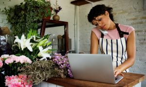 Woman wearing pink tshirt and stripy apron on telephone and typing at a laptop in a florist