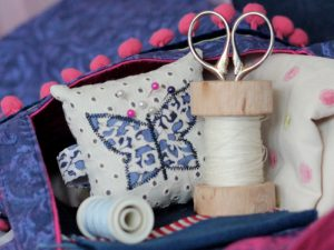 White pin cushion with reel of thread and scissors