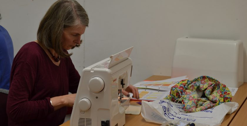 Lady in burgundy sweater working with sewing machine