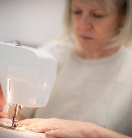 Woman in muslin pattern using sewing machine