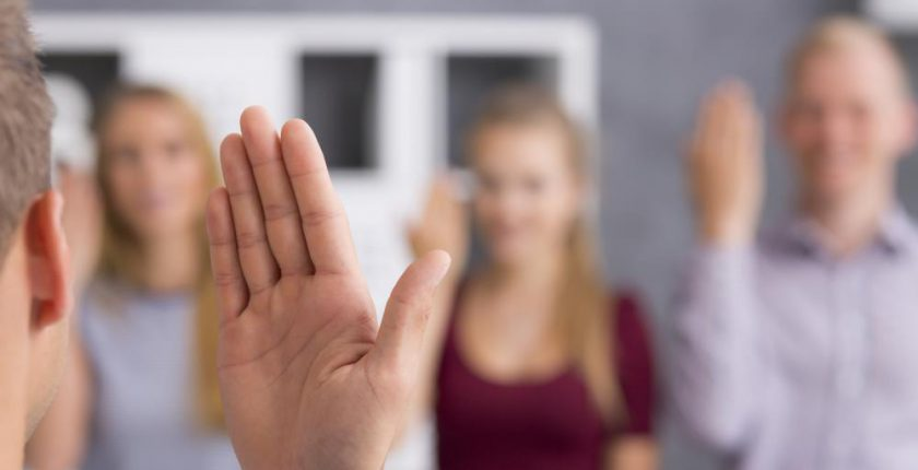 Hand using sign language with three people in background
