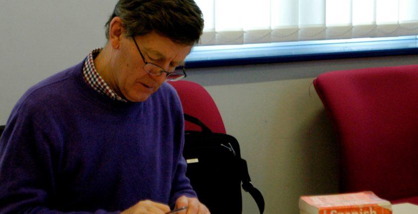 Man in blue sweater reading Spanish