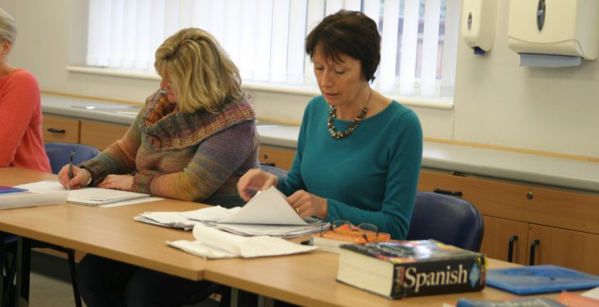 Two women learning Spanish in a classroom