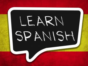 Learn spanish text in speech bubble in front of Spanish flag