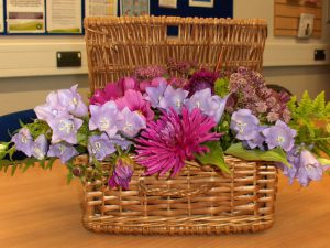 Pink and purple flower arrangement in wicker basket