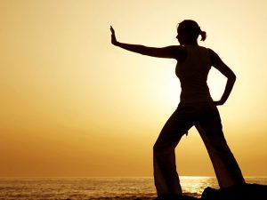 woman practising tai chi with a sunset