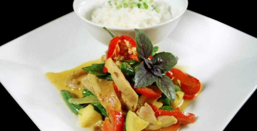 Thai red curry and bowl of rice on white square plate