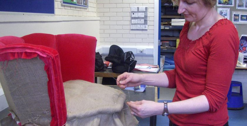 Woman reupholstering a chair