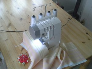 Overlocker sewing machine on wooden table with cloth and pincushion