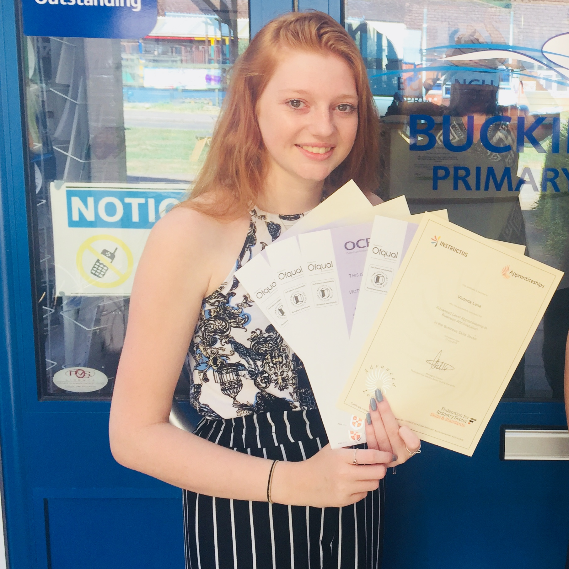 Girl with red hair holding certificates outside a door