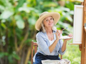 Woman in a hat painting on an easel outside
