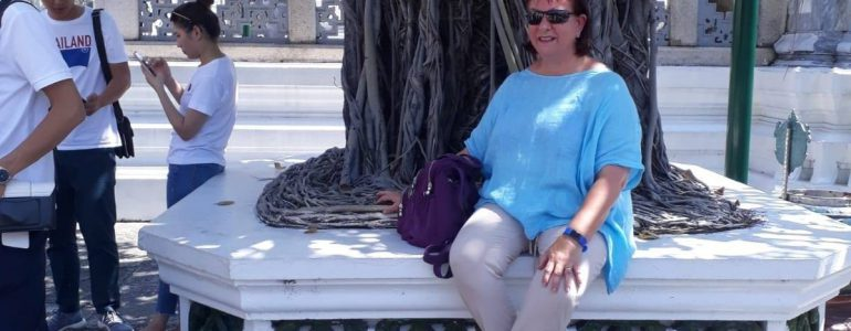 Lady in blue top wearing sunglasses underneath a tree