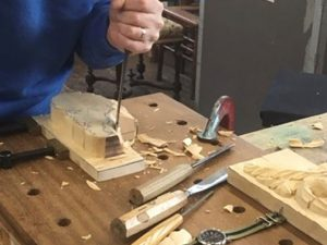 Man in blue sweater wood carving with chisel