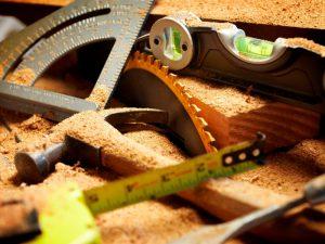 Hammer, tape measure, spirit level covered in sawdust