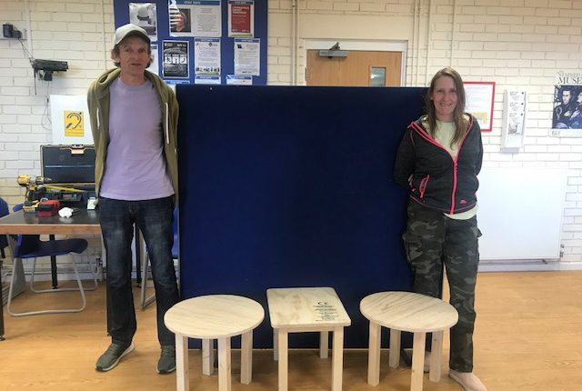 A man and a woman with three wooden tables that they made