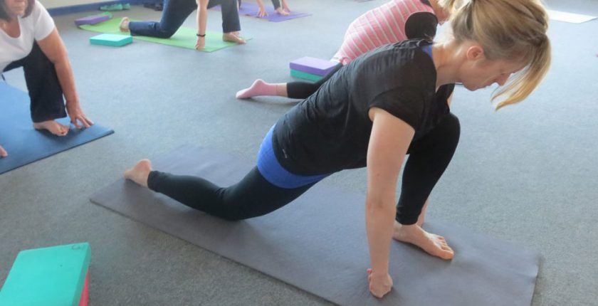 Woman practising yoga on yoga mat