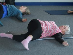 Two women lying down on yoga mats