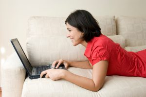 Woman using laptop lying on a sofa