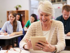 Woman in classroom on ipad with other people behind