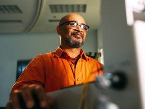 man wearing eyeglasses facing computer