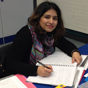 Women student smiling and writing notes in her notepad on a desk at Buckinghamshire Adult Learning