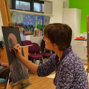 Adult Learner Student painting on a canvas in a Art class